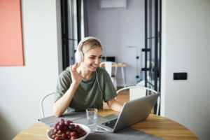 Cheerful girl in headphones waving her hand to friend during video-chatting