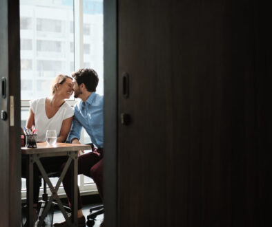 Two Co-Workers Sitting At Office Desk And Kissing