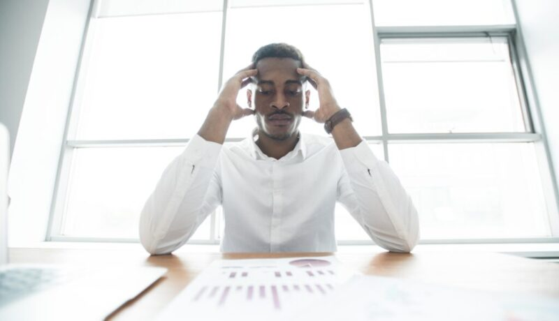 puzzled-african-businessman-analyzing-graphs-9TZHXMC72